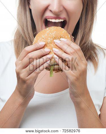 Girl eating big burger on white background