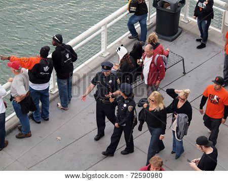 Male And Female Sfpd Police Officers Walk Down Promenade Along Water