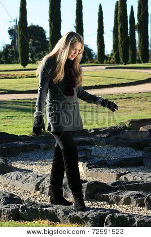 Girl Walking On Rocks In Park