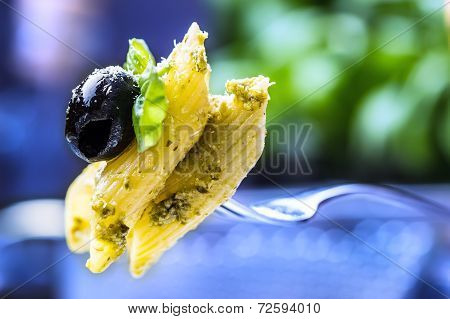 Serving of penne pasta on a fork with basil leaves and black olive.