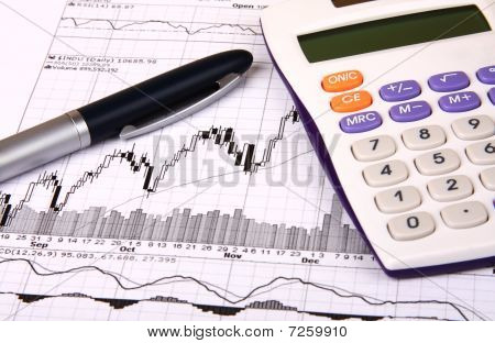 White Calculator And A Blue Pen On A Financial Chart