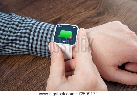 Male Hands With White Smartwatch With Message On The Screen Over A Wooden Table