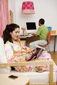 foto of futon  - A woman reads a magazine and listens to music on a futon while her husband works on a computer in the background - JPG