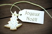 image of christmas cookie  - A Christmas Tree Cookie with a Label with the French Words Joyeux Noel on it which means Merry Christmas