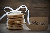 stock photo of ginger bread  - Ginger Bread Cookies with white Ribbon and Bow and Label on which the French Words Merci stands which means Thank You