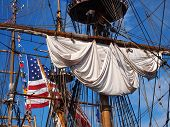stock photo of tall ship  - Looking up into the rigging and masts of a tall ship a rolled up sail a large American flag and many small international flags can be seen against a vibrant blue sky - JPG
