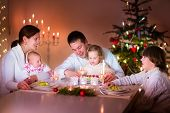 image of christmas baby  - Big happy young family with three children enjoying Christmas dinner celebration parents and kids  - JPG