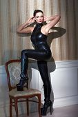 stock photo of catsuit  - Sexy woman posing at vintage wall in latex catsuit - JPG