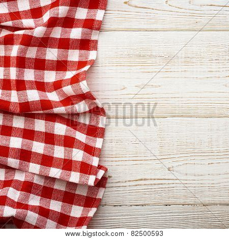 Top view of checkered tablecloth on white wooden table. square