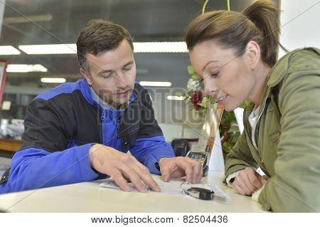 Mechanic showing repair bill to car owner