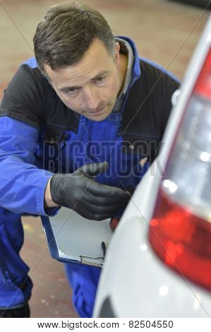 Mechanic checking on auto bodywork
