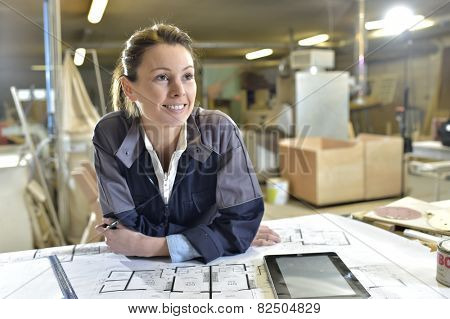 Young woman carpenter designing plans in workshop
