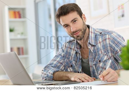 Home-office worker taking notes on paper