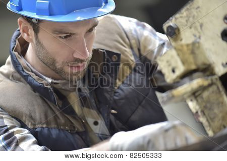 Industrial worker working on machine in factory