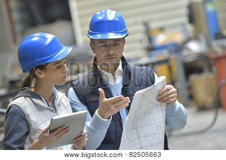 Engineers in mechanical factory reading instructions
