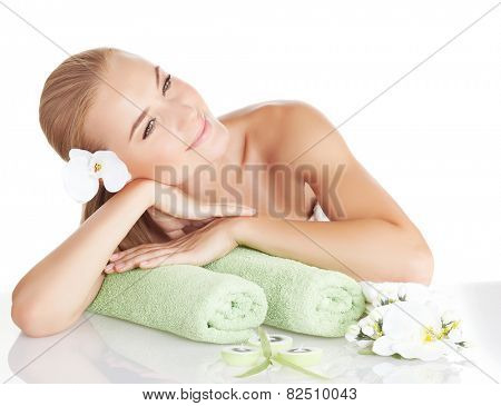 Beautiful blond woman with gentle orchid flower in hair isolated on white background, enjoying day spa, relaxing on massage table, medical beauty treatment, well being lifestyle