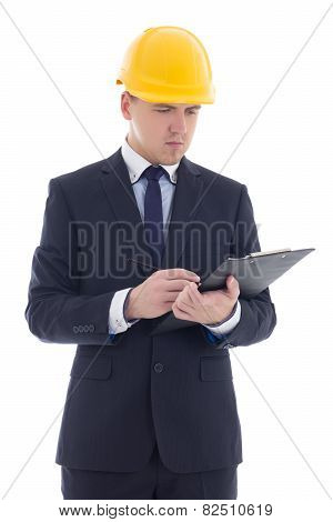 Young Handsome Business Man In Yellow Builder's Helmet Writing Something Isolated On White