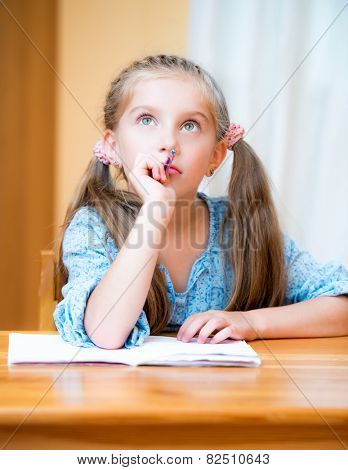 Cute pensive little girl studying at home and smiling