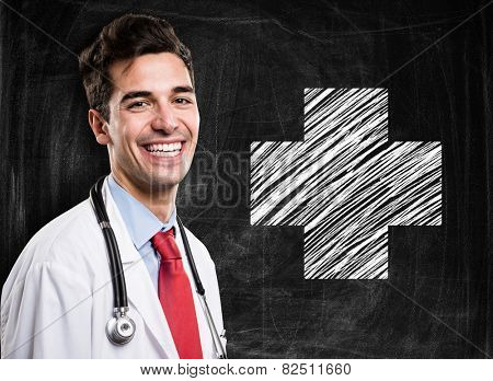 Portrait of a smiling doctor in front of a blackboard