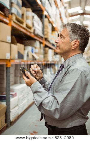Focused male manager using handheld in a large warehouse