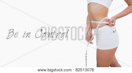 Midsection of fit woman measuring waist over white background