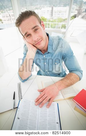 Exhausted businessman studying at his desk in his office