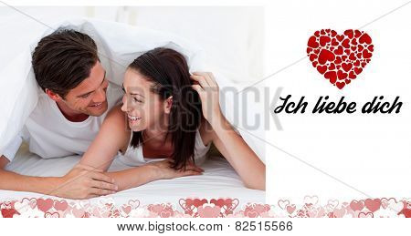 Couple talking together and lying on bed against ich liebe dich