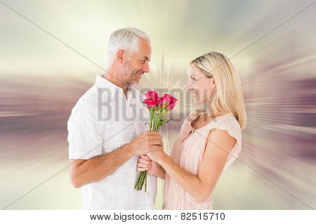 Affectionate man offering his partner roses against room with large window looking on city