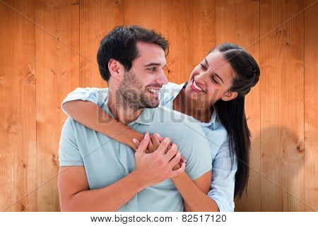 Cute couple smiling at each other against wooden planks