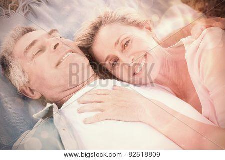 Happy senior couple cuddling on blanket on a sunny day