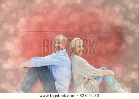 Happy mature couple smiling at camera against light glowing dots design pattern