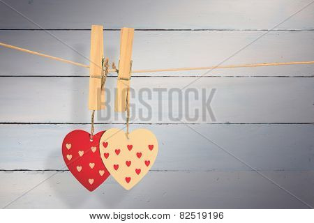 Hearts hanging on the line against painted blue wooden planks