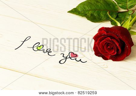 i love you against red rose on wood