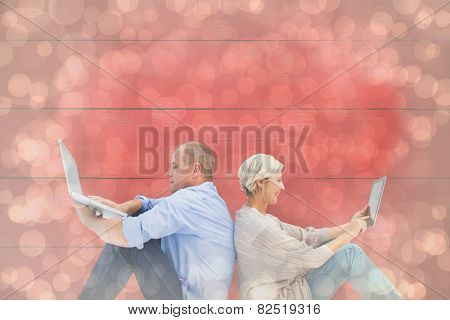 Mature couple using laptop and tablet pc against light glowing dots design pattern