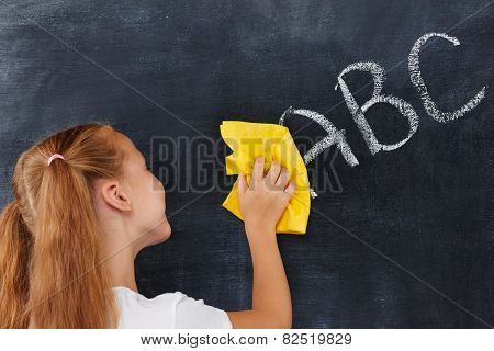 Pretty industrious redhead girl smiling an cleaning blackboard