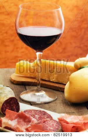 Selection Of Cheese And Ham With Glass Of Red Wine