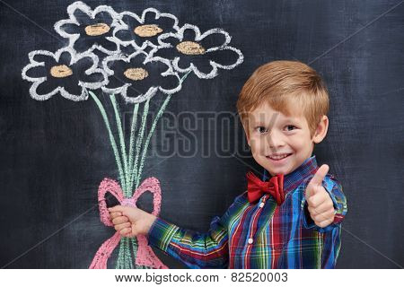 Cute playful ginger boy presenting pictured bouquet and showing