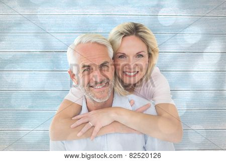 Smiling couple embracing and looking at camera against light circles on grey background