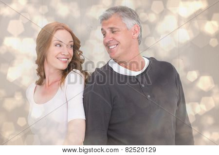 Casual couple smiling at each other against light glowing dots design pattern
