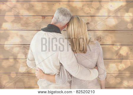 Happy couple standing with arms around against light glowing dots design pattern