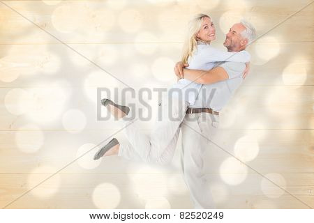 Man picking up his partner while hugging here against light circles on grey background