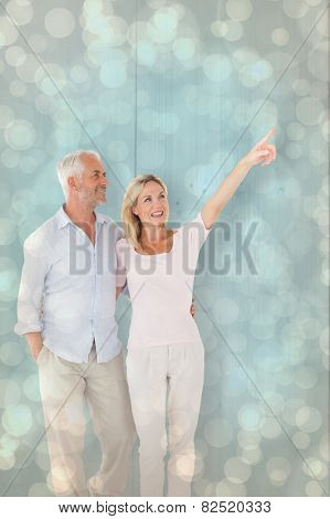 Smiling couple walking and pointing against light glowing dots design pattern