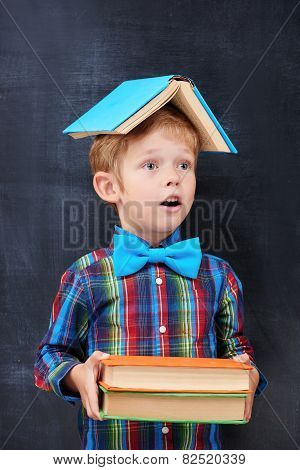 Mixed-up ginger school-boy overloaded with books