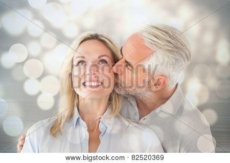 Affectionate man kissing his wife on the cheek against light circles on bright background