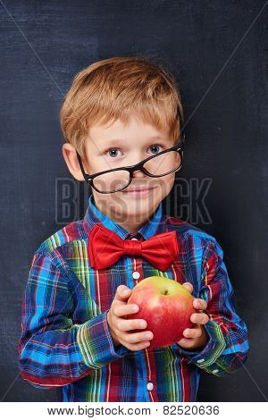 Mixed-up ginger primary school age boy holding red apple
