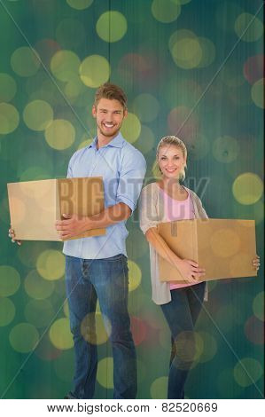 Attractive young couple carrying moving boxes against close up of christmas lights