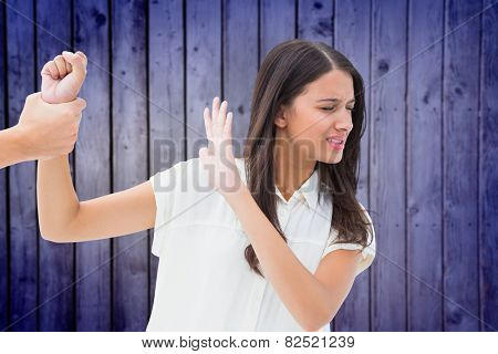Fearful brunette being grabbed by the hand against wooden planks background