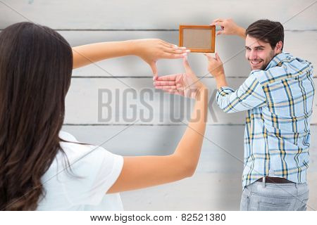 Happy young couple putting up picture frame against painted blue wooden planks