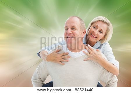 Happy mature man giving piggy back to partner against digitally generated dandelion seeds on green background