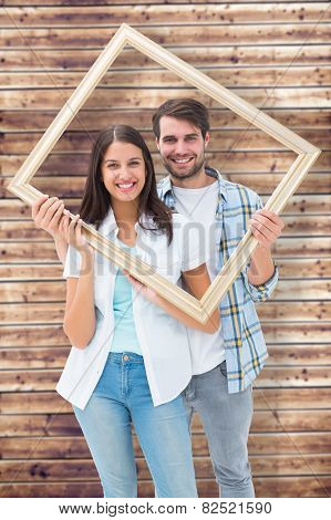 Happy young couple holding picture frame against wooden planks